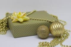 Boîte-cadeau et deux boules de Noël sur un fond clair Image stock