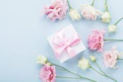 Boîte-cadeau et fleurs en pastel pour le jour de mères sur la vue supérieure bleue de table style plat de configuration photographie stock