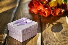 Boîte-cadeau et fleurs sur la table en bois Image stock