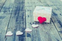 Boîte-cadeau et forme rouge de coeur sur le bois Image libre de droits