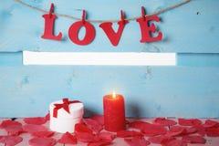 Boîte-cadeau et l'amour de mot dans la lueur d'une bougie Photo stock
