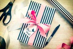 Boîte-cadeau et matériaux d'emballage sur un vieux fond en bois blanc Note de salutation attachée plus de Type de cru Images stock