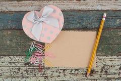 Boîte-cadeau et papier de coeur sur la table en bois de vintage pour votre amour Image stock