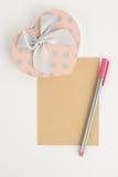 Boîte-cadeau et papier de coeur sur le fond blanc Image stock