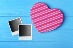 Boîte-cadeau et photos en forme de coeur sur le fond en bois bleu Photographie stock libre de droits