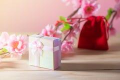 Boîte-cadeau et sac rouge de cadeau enveloppés et présents de Noël et de Newyear de fleur de prune avec des arcs et des rubans, b Photographie stock