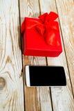 Boîte-cadeau et téléphone sur le fond en bois Photographie stock
