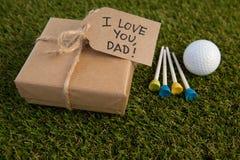 Boîte-cadeau et texte de jour de pères par la boule de golf sur le champ Photographie stock