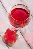 Boîte-cadeau et verre de vin rose Photo libre de droits