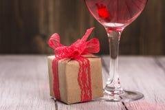 Boîte-cadeau et verre de vin rose Image stock
