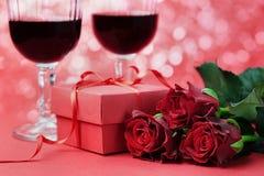 Boîte-cadeau, fleurs de roses rouges et deux verres de vin Images libres de droits