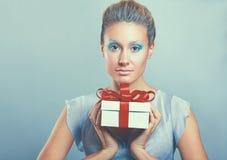 Boîte-cadeau heureux de prise de sourire de jeune femme dans des mains, d'isolement au-dessus du fond gris Photo stock