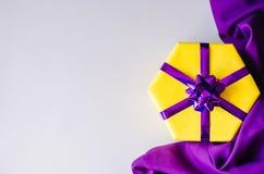 Boîte-cadeau jaune avec un arc pourpre photographie stock libre de droits