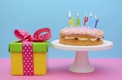 Boîte-cadeau lumineux de couleur avec le gâteau et les bougies Image libre de droits