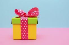 Boîte-cadeau lumineux de couleur sur le fond rose et bleu Photographie stock libre de droits
