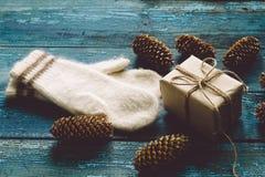 Boîte-cadeau, mitaines blanches et cônes d'arbre de Noël Photographie stock