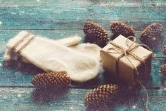 Boîte-cadeau, mitaines et cônes de pin sur conseils en bois bleus Photographie stock
