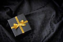 Boîte-cadeau noir avec l'arc d'or de ruban Image libre de droits