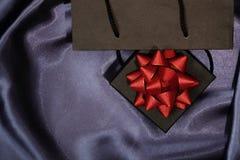 Boîte-cadeau noir avec le sac à provisions noir sur le tissu foncé photo stock