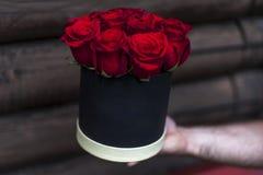 Boîte-cadeau noir avec les roses rouges dans des mains humaines Photographie stock