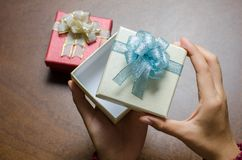 Boîte-cadeau ouvert de main sur le fond en bois Images libres de droits