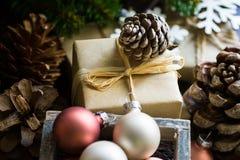 Boîte-cadeau pendant Noël et la nouvelle année enveloppés en papier de métier, cônes de pin, branches d'arbre de sapin, babioles  Images libres de droits
