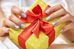 Boîte-cadeau pointillé dans des mains femelles Photos stock