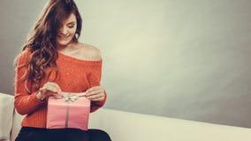 Boîte-cadeau rose actuel s'ouvrant de fille Photo stock