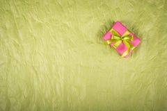 Boîte-cadeau rose avec le ruban vert sur un fond de papier fripé Fond de papier chiffonné par vert Copiez l'espace Photos libres de droits