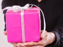 Boîte-cadeau rose dans des mains masculines Images stock