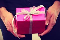 Boîte-cadeau rose dans des mains masculines Photographie stock libre de droits