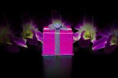Boîte-cadeau rose sur l'orchidée pourpre de Dendrobium de beauté de tache floue Photo libre de droits