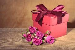 Boîte-cadeau rouge attaché avec la fleur rose décorative de ruban et de bouquet Photographie stock
