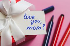 Boîte-cadeau rouge attaché avec un ruban blanc, des marqueurs et une carte avec une inscription sur un fond rose image stock