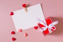 Boîte-cadeau rouge avec l'arc, calibre de papeterie/photo avec la bride et petits coeurs Photo libre de droits