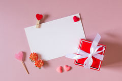 Boîte-cadeau rouge avec l'arc, calibre de papeterie/photo/carte postale avec la bride, petits coeurs, sucrerie, et fleurs de ress Image stock