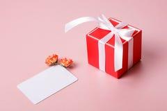 Boîte-cadeau rouge avec le calibre d'arc, de carte de crédit/de visite et les fleurs de ressort Photographie stock libre de droits