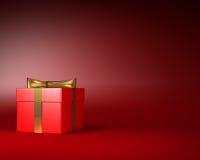 Boîte-cadeau rouge avec le ruban d'or et arc sur le fond rouge Photo libre de droits