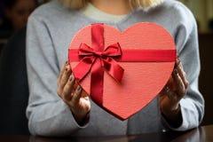 Boîte-cadeau rouge avec le ruban sous forme de coeur chez des mains de la femme f Photos stock