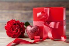 Boîte-cadeau rouge, coeur de scintillement et fleur rose sur le fond en bois Carte de voeux de jour de mère ou de valentines Images libres de droits