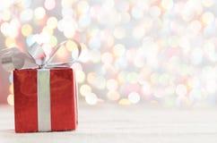 Boîte-cadeau rouge décoratif avec un grands arc et fond argentés b photographie stock
