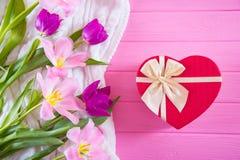 Boîte-cadeau rouge dans la forme du bouquet de coeur et d'offre de belles tulipes sur le fond en bois rose Photo stock