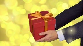Boîte-cadeau rouge de deux prises masculines de mains avec l'arc d'or Célébrez le boîte-cadeau actuel de la veille Homme caucasie banque de vidéos