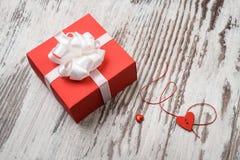 Boîte-cadeau rouge de jour de valentines sur le conseil en bois Image libre de droits