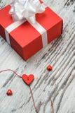 Boîte-cadeau rouge de jour de valentines sur le conseil en bois Images libres de droits