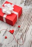 Boîte-cadeau rouge de jour de valentines sur le conseil en bois Image stock