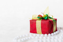 Boîte-cadeau rouge de Noël avec le ruban et les perles argentés brillants Photographie stock