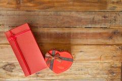 Boîte-cadeau rouge et coeur de ruban et mini rouge à l'intérieur sur le backgr en bois Photographie stock libre de droits