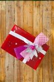 Boîte-cadeau rouge et coeur de ruban et mini rouge à l'intérieur sur le backgr en bois Images libres de droits
