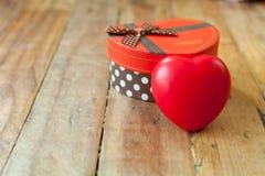 Boîte-cadeau rouge et coeur de ruban et mini rouge à l'intérieur sur le backgr en bois Photo stock